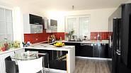Kuchyně je zařízena moderně v černo-červených barvách, které doplňuje barva bílá.