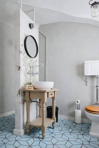 Na podlaze v koupelně je cementová dlažba. Ve sprchovém koutu je na stěně epoxidová stěrka, sloup zdobí tapeta. Foto: Thomas Skovsende