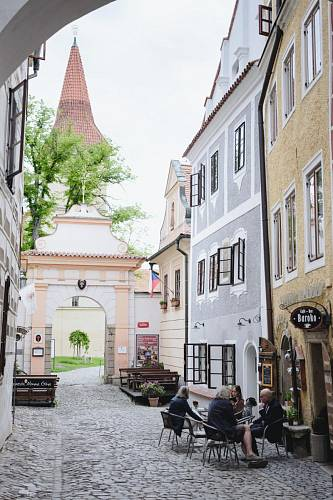 Ulice Klášterní, pohled na vstupní bránu do klášterních zahrad, šedobílý dům na pravé straně je Monastery Garden / Bistro & Rooms. Na fasádě je freska Svaté rodiny.  Foto: Thomas Skovsende