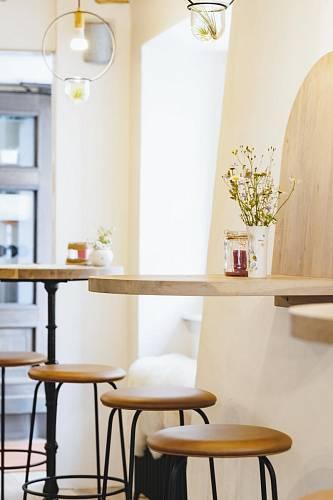 Vyvýšené sezení u barových stolků. Dva stolky jsou na podnoži před oknem, jeden je zavěšený na stěně. Podnože jsou litinové, desky z dubu.  Pod okny jsou litinové radiátory s kůží, které jsou také určeny k sezení. Foto: Thomas Skovsende...