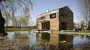 Dům na břehu jezírka obklopeného stromy má dřevěnou fasádu. Své okolí tedy nenarušuje.