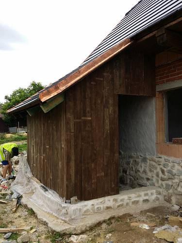 Obklady z kamene, falešné roubení, dřevěná konstrukce a betonová taška Tegalit s plochým profilem působí autenticky
