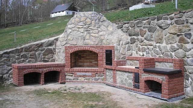 Velkorysá rustikální venkovní kuchyně s otevřeným ohništěm skrývá výkonné moderní topidlo a dostatek místa na uložení dřeva i přípravu pokrmů.