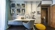 Tapeta a povrchy skříněk kolem pracovního stolku mají vzhled a barevnost připomínající beton.