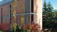 Po realizaci - Již zmíněné sloupovité habry pocitově snižují výšku sousední budovy a rozkvetlý bujně rostoucí záhon trvalek odvání pozornost od staveniště.