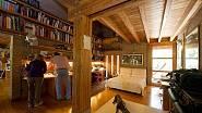 Knihovna je netypicky umístěná ve dvou pruzích nade dveřmi. V interiéru převládá dřevo.