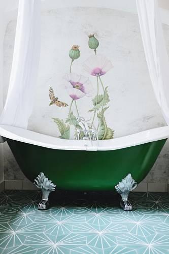 Koupelna je ukrytá za skříní. Na podlaze je cementová dlažba, za vanou omyvatelná tapeta. Foto: PURPLE