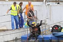 Chodci na nábřeží řeky Ohře v Terezíně můžou v těchto dnech  sledovat práce dělníků i potápěče při kontrole a údržbě klapek zdejšího jezu.
