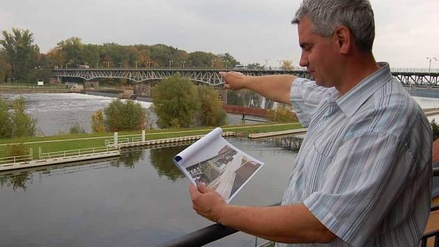 Jiří Šikula ze společnosti Povodí Labe ukazuje místo, kde by plánovaná vodní elektrárna měla stát. V ruce drží počítačovou studii vodního díla.