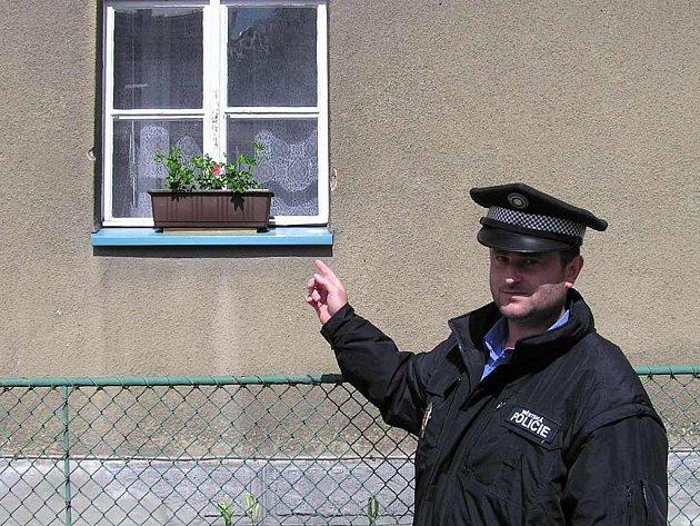 Strážník ukazuje okno domu v Dlouhé ulici,  do jehož blízkosti  v neděli  dopadaly střely.