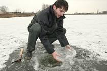 VRSTVA LEDU. Rybáři musejí nyní vyrážet i každý den vysekávat otvory do zamrzlých rybníků a nádrží, jinak by se ryby udusily. Na snímku je lovosický rybář Michal Řepík při vysekávání těchto otvorů do zamrzlé sulejovické nádrže.