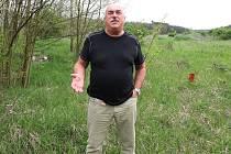 """SKLÁDKA. Travčický starosta Miloš Řepa stojí v místech, kde je nebezpečná skládka patřící Lovosicím. Prostor není nijak oplocen. Pod """"zelenou"""" vrstvou se ale skrývá nebezpečí v podobě ekologických rizik. Přitom jen pár metrů odsud jsou první domy."""