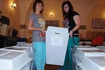 V zasedací síni Městského úřadu v Litoměřicích chystají  studentky střední školy volební urny pro jednotlivé volební okrsky.