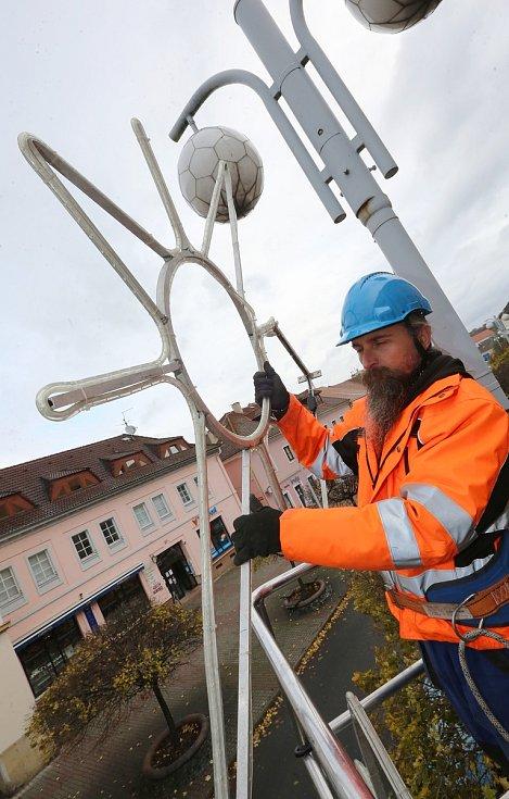 Pracovníci technických služeb začali s montáží vánoční výzdoby na sloupy veřejného osvětlení. Na snímku Martin Česal montuje vánoční hvězdu v ulici Dlouhá.