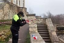 Strážník páskou označuje místo havárie schodišťového zdiva vedoucího od divadla kbývalému železničnímu tunelu na parkánech v Litoměřicích