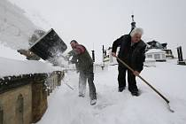 Zaměstnanci shazují hromadící se sníh z rovné střechy státního zámku Ploskovice