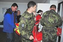 Senátor a místopředseda vlády ČR Alexandr Vondra (vlevo) a náměstek ministryně obrany Martin Barták (druhý zleva) pomáhají s transportem turistky k vojenskému vrtulníku.
