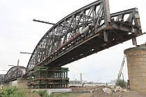 PRVNÍ ze tří obloukových nosníků železničního mostu přes Labe stavbaři v sobotu demontovali ze soulodí.