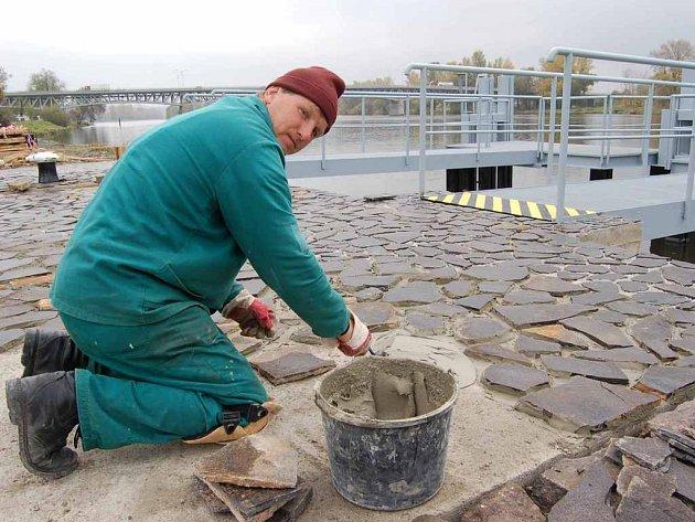 Jozef Jaščo dokončuje dláždění štípaným kamenem.