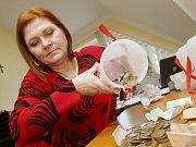 Koordinátorka Tříkrálové sbírky Farní charity z Litoměřic Naděžda Kejkrtová vysypává jednotlivé kasičky.