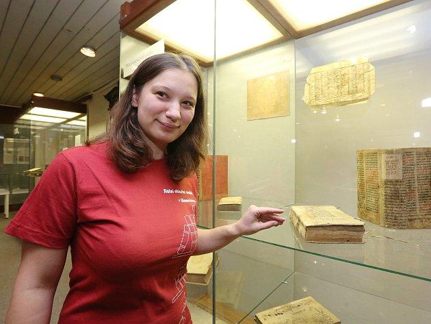 Restaurátorka Pavlína Bártová ukazuje vystavené historické knihy s barokní vazbou.