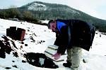 ZIMA NEZIMA, na Hřbitově zvířat se pohřbívá i přes zimu, kdy na něm leží sněhová peřina a země bývá zmrzlá. Na snímku pomocník majitele hřbitova a smuteční řečník Jan Figr, kopec za ním je hora Říp z pohledu, který je obecně méně známý.