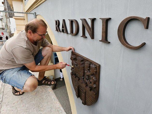 Akademický sochař Libor Pisklák instaluje označení na budovu Městského úřadu v Litoměřicích na Mírovém náměstí
