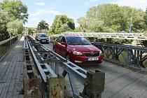 Provizorní most před řeku Ohře v Břežanech mohou využívat osobní auta, autobusy a vozidla IZS. Provoz na mostě nyní řídí semafor. Řidiči nákladních aut musejí využít stanovenou objízdnou trasu. Nový most má být dokončený v září.
