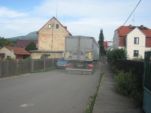 Vulici se dvě nákladní vozidla minou jen těsně, vzdálenost od oken domu pak činí zhruba jeden metr.