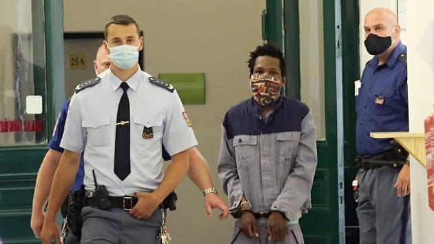 Eskorta přivádí obžalovaného A. I. Dialla k soudu v Litoměřicích