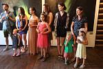 Umělci i hosté na vernisáži výstavy mladých výtvarníků Litoměřicka se v parném dni vernisáže ovívají pozvánkami na tuto akci.