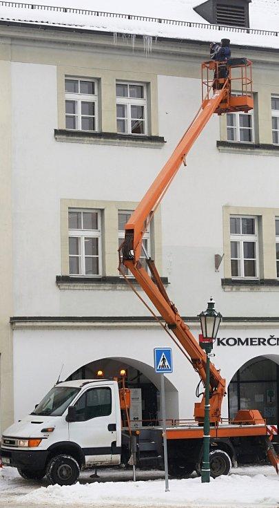 Odborná firma v Litoměřicích s pomocí plošiny likviduje rampouchy visící ze střech