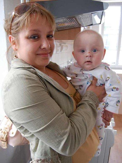 NOVÝ DOMOV.  Anna Grigorijeva drží v náručí ve svém novém bytě ve Velešicích u  Hoštky pětiměsíční Zlatku Petrovou,  která včera spolu s rodiči odjížděla do nového domova v Podsedicích.