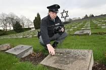 Na snímku policista ukazuje jeden ze zničených náhrobků.