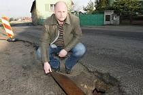 Zima se podepsala na silnici ve Vetlé. Pod krajnicí vede kanalizace z rybníka, kterou je potřeba opravit. Starosta obce Vlastimil Mikl ukazuje, jak je stoka hluboká.