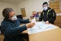 Pracovníci potravinové banky v Litoměřicích vydávají ze skladu ochranné roušky pro sociálně slabé občany ve Šluknovském výběžku.