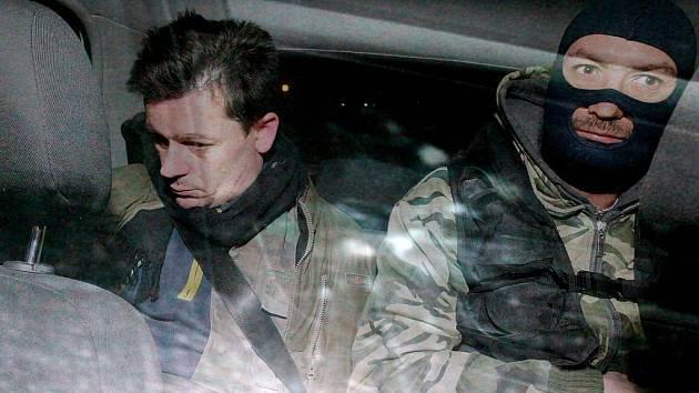 Jednoho ze zadržených pachatelů převáží litoměřičtí policisté k výslechu.