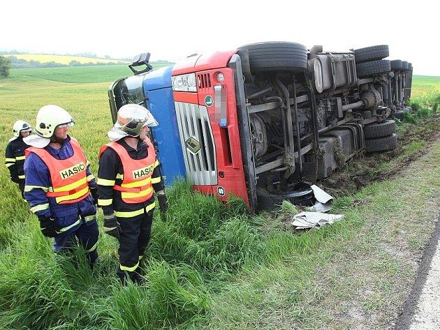 Kamion s naloženým papírem se převrátil do pole
