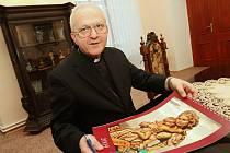 BISKUP.  Mons. Jan Baxant drží v rukou kalendář pro rok 2009 se svým biskupským znakem a heslem  UT VIDEAM (Ať vidím)