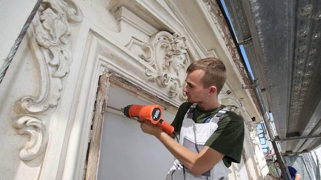 Řemeslníci pracují na obnově fasády a dřevěných oken zámku v Ploskovicích