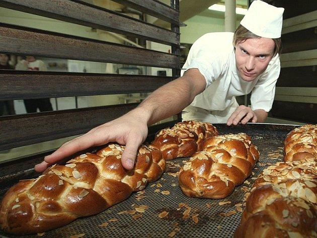 PŘEDVÁNOČNÍ SHON. Toho si v těchto dnech užijí v pekárnách požehnaně. Kromě cukroví, jehož výrobu dnes už řada žen nechává na odbornících,  jsou v kurzu klasické vánočky. Petr Černý z lovosické Cukrárny a pekařství Vladimír John jich peče denně stovky.