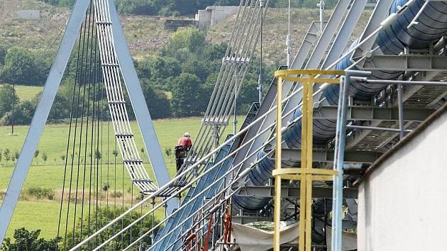 PAVOUČÍ MUŽI odvádějí špinavou práci na natírání mostu pro vodovodní potrubí ve výšce 15 až 40 metrů nad hladinou Labe. Provedení kompletní údržby potrvá měsíce.