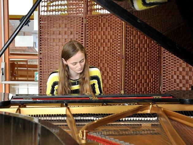 Ondřej Slavík, Adéla Grindlerová (na snímku) a Lukáš Kacar, žáci ZUŠ Litoměřice, přišli seniorům zahrát na klavír.