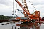 Obří díl regulačního transformátoru v Lovosicích přeložili odborníci z lodě na nákladní automobil.