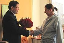 Ředitel Leoš Vysoudil předává mamince prvního miminka květiny.