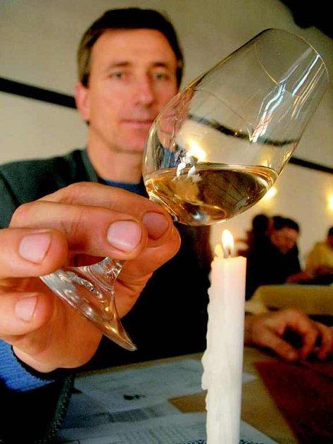 Stanislav Rudolfský z vinných sklepů v Kutné Hoře hodnotí přes světlo svíčky čirost a barvu jednoho ze soutěžních vín.