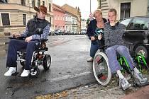 Matka postiženého chlapce Eva Klabanová ukazuje na rozhraní ulice Rooseveltovy a Osvobození, kolik sil musí vynaložit, aby se dostala na chodník. Vedle ní sedící Milan Tatarkovič to s mechanickým vozíkem nezvládne vůbec.
