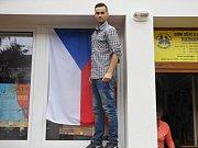 Mladý Litoměřičan Martin z volební komise finišoval na přípravu volební místnosti v Domě dětí a mládeže Rozmarýn v Litoměřicích. Aby lidé trefili, pověsil i vlajku do okna.