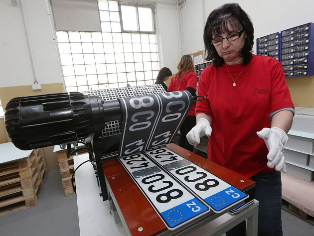 Výroba registračních značek pro motorová vozidla ve Štětí. Pracovnice firmy Edita Srbová vyndavá dvojici potažených značek.