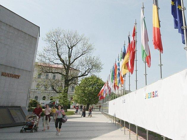 Pracovníci odborné firmy instalují vlajky členských zemí EU na střeše domu kultury.